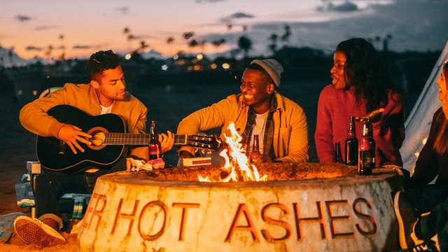 """Friends playing guitar and socializing in front of a campfire in a pit with the words """"HOT ASHES."""""""