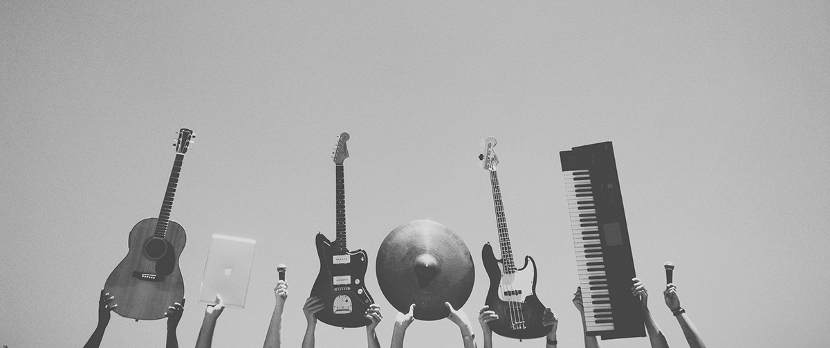 Black and white photo of hands holding up instruments: acoustic guitar, laptop, mic, electric guitar, cymbal, bass, keyboard, mic.